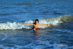 Child playing in sea jumping the waves Stock Photography