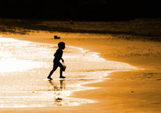 Child playing on the seashore. In the evening Royalty Free Stock Photography