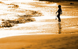 Child playing on the seashore. In the evening Stock Images