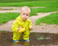 Child playing with ship in the puddle outdoor. Little child playing with ship in the puddle outdoor. Spring season Royalty Free Stock Photography