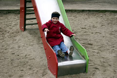 Child playing on slide. Child playing on red and green slide Stock Images