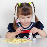 Child playing with small toys at table Stock Photos