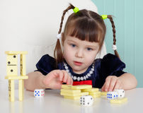 Child playing with small toys at table Stock Photo
