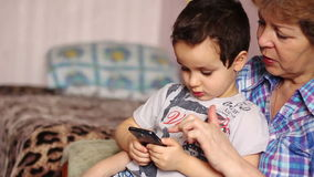 Child playing with a smartphone and grandmother stock footage
