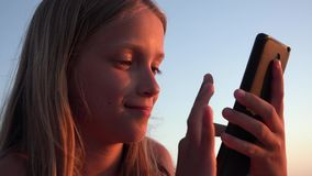 Child playing smartphone, kid on beach at sunset, girl using tablet on seashore.  stock footage