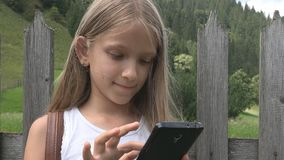 Child playing smartphone outdoor, kid browsing tablet, girl relaxing in nature stock video