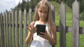 Child Playing Smartphone Outdoor, Kid on Tablet, Girl Relaxing in Nature stock photos