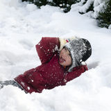 Child playing in snow. Happy child, boy or girl, playing in a deep fresh snow in a winter garden Stock Photos