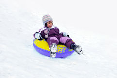 Child playing in snow. Young girl sliding down snow covered slope in inflatable tube Stock Images
