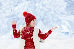 Child playing in snow on Christmas. Kids in winter royalty free stock photos