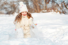 Child playing with a snow enjoying nature on a winter walk in su Stock Photos