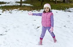Child playing in the snow in the park Stock Photos