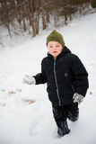Child playing in snow running Stock Photography