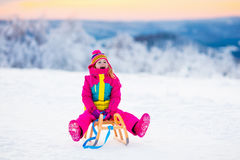 Child playing in snow on sleigh in winter park Royalty Free Stock Image