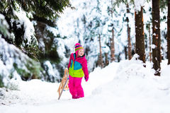 Child playing in snow on sleigh in winter park Stock Image