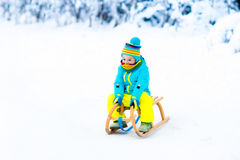 Child playing in snow on sleigh in winter park Stock Photography