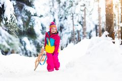 Child playing in snow on sleigh in winter park Royalty Free Stock Photo