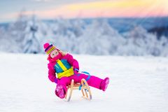 Child playing in snow on sleigh in winter park Royalty Free Stock Images