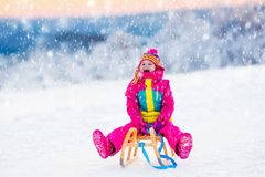 Child playing in snow on sleigh in winter park Stock Images