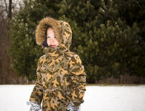 Child Playing in the Snow. Child in winter coat playing outside in the cold Snow Royalty Free Stock Photo
