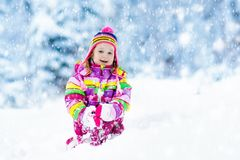Child playing with snow in winter. Kids outdoors. Royalty Free Stock Images