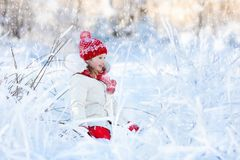 Child playing with snow in winter. Kids outdoors. Stock Photo