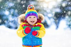 Child playing with snow in winter. Kids outdoors. Royalty Free Stock Photography