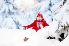 Child playing with snow in winter.Boy in snowy park. Stock Photos