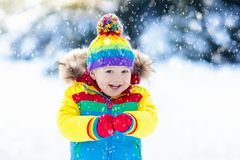 Child playing with snow in winter. Kids outdoors. Stock Photography
