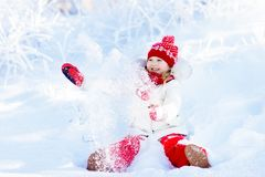 Child playing with snow in winter. Kids outdoors. Royalty Free Stock Photo