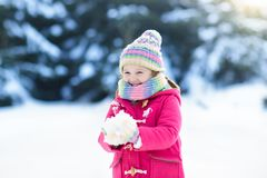Child playing with snow in winter. Kids outdoors. Stock Images