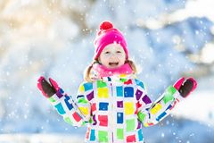 Child playing with snow in winter. Kids outdoors. Child playing with snow in winter. Little girl in colorful jacket and knitted hat catching snowflakes in Stock Image