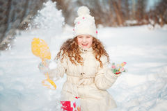 Child playing with a snow on a winter walk in the park. Royalty Free Stock Photography