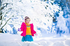Child playing in snowy winter park Royalty Free Stock Image
