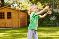 Child playing with soap bubbles. Small child playing with soap bubbles in the garden Royalty Free Stock Photography