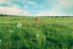 Child playing among soap bubbles in summer Stock Images