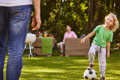 Child playing soccer ball. With father in garden Stock Photo