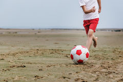 Child playing soccer on beach. Royalty Free Stock Photos