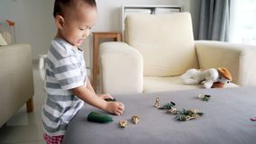 Child playing soldiers and figurine toys stock video