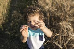 Child playing with some snails. Child playing with some snails at sunset with a field of wheat in the background Stock Images