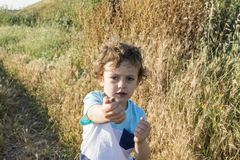 Child playing with some snails. Child playing with some snails at sunset with wild herbs in the background Stock Image