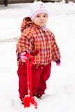 Child playing with spade in snow Stock Image