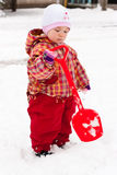 Child playing with spade in snow Royalty Free Stock Photography