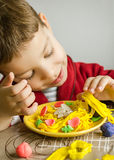 Child playing with spaghetti dish made with plasticine royalty free stock image