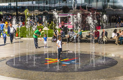 Child playing with springing water. Playful boy child surrounded by water springing from a ground fountain on May 1, 2014 in Bucharest, Romania Stock Photography
