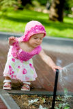 A child playing with sprinkler. A pretty kid girl playing with sprinkler royalty free stock photography