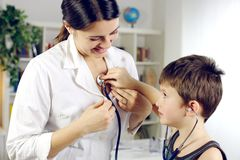 Child playing with stethoscope on female happy doctor Royalty Free Stock Photography