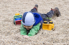 Child playing in stones pebbles at playground Stock Photos