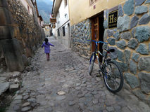 Child Playing on Street in Ollantaytambo. A young Peruvian girl walks down a cobblestone street in the ancient city of Ollantaytambo, Peru Stock Photography
