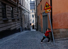Child playing in street. Propping up school crossing sign in Gamla Stan, Stockholm, Sweden Royalty Free Stock Photos